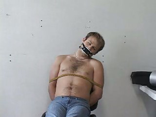 heres a male tied up and with a gag inside his
